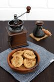 Homemade cookies in a wooden cup with a coffee mill and coffe pot. On white brick background Royalty Free Stock Image