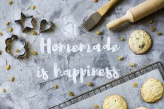 Homemade cooking concept. Word Homemade is written on a gray concrete background of flour. Next to the baking sheet with biscuits, shapes and rolling-pin Royalty Free Stock Photo