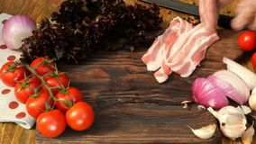 Homemade cooking. Products for delicious food. Human hands lay sliced raw pork or beef brisket on wooden kitchen board. Vegetables: tomatoes, lettuce, onion stock video footage