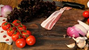 Homemade cooking. Products for delicious food. Human hands lay sliced raw pork or beef brisket on wooden kitchen board. Vegetables: tomatoes, lettuce, onion stock video