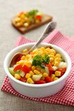 Homemade corn salsa in white bowl with spoon Stock Photo