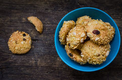 Homemade cornflakes cookies. Pile of homemade cornflakes and raisins cookies in a blue bowl on old wooden table with place for text. Freshly baked corn flake Stock Photography