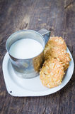 Homemade cornflakes cookies. Homemade cornflakes and raisins cookies with cup of milk on old wooden table. Freshly baked corn flake cereal cookies on rustic Royalty Free Stock Photos
