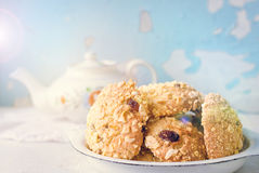 Homemade cornflakes cookies. Homemade cornflakes and raisins cookies with tea pot on old wall background. Freshly baked corn flake cereal cookies in rustic style Royalty Free Stock Image
