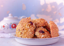 Homemade cornflakes cookies. Homemade cornflakes and raisins cookies with tea pot on old wall background. Freshly baked corn flake cereal cookies in rustic style Stock Image