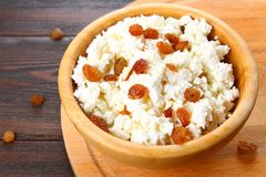 Homemade cottage cheese with almonds and raisins in a bowl on a wooden table. Homemade cottage cheese with almonds and raisins in a bowl on a wooden table Stock Images