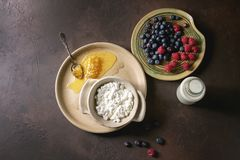 Homemade cottage cheese. Ceramic bowl of homemade cottage cheese served with blueberries, raspberries, bottle of milk and honeycombs over dark brown texture Royalty Free Stock Photo