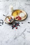 Homemade cottage cheese. Ceramic bowl of homemade cottage cheese served with blueberries, raspberries, bottle of milk and honeycombs over white marble texture Royalty Free Stock Photos