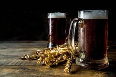 Homemade craft beer mugs. Two Homemade craft beer mugs, dark wooden background copy space royalty free stock photography