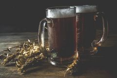 Homemade craft beer mugs. Two Homemade craft beer mugs, dark wooden background copy space royalty free stock photos