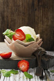Homemade cream ice cream from organic cow cream in a vintage ceramic vase with fresh strawberries and melissa in rustic. Style. Selective focus Royalty Free Stock Photography