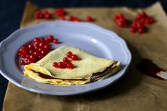 Crepes. Homemade crepes with chocolate spread and red currants. Selective focus royalty free stock photography