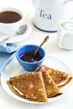 Homemade crepes folded in triangles with black currant jam. royalty free stock images