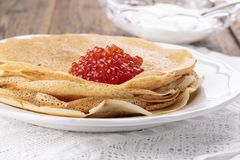 Homemade crepes with red caviar royalty free stock photography
