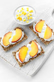 Homemade Crispbread toast with Cottage Cheese and nectarine on white wooden board. Stock Image