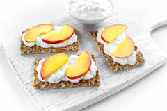 Homemade Crispbread toast with Cottage Cheese and nectarine on white wooden board. Royalty Free Stock Photo