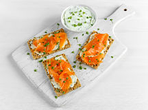 Homemade Crispbread toast with Smoked Salmon, Melted Cheese and cress salad. on white wooden board Stock Photos