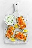 Homemade Crispbread toast with Smoked Salmon, Melted Cheese and cress salad. on white wooden board background. Stock Images