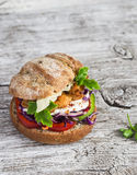 Homemade crispy fish burger on a  rustic wooden board Royalty Free Stock Image