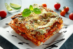Homemade Crispy lasagna in iron pan with minced beef bolognese sauce, parmesan cheese and basil Royalty Free Stock Images