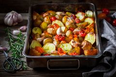 Homemade and crispy roasted potato with garlic, tomato and rosemary Stock Photography