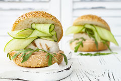 Homemade crispy spring fish burger with spicy chilli mayo on white rustic wooden board over light background. Copy space. Homemade crispy spring fish burger Royalty Free Stock Photography