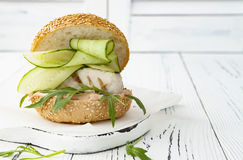 Homemade crispy spring fish burger with spicy chilli mayo on white rustic wooden board over light background. Copy space. Homemade crispy spring fish burger Stock Photography