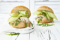 Homemade crispy spring fish burger with spicy chilli mayo on white rustic wooden board over light background. Copy space. Homemade crispy spring fish burger Royalty Free Stock Photos