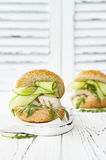 Homemade crispy spring fish burger with spicy chilli mayo on white rustic wooden board over light background. Copy space. Homemade crispy spring fish burger Stock Photo