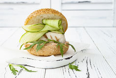 Homemade crispy spring fish burger with spicy chilli mayo on white rustic wooden board over light background. Copy space. Homemade crispy spring fish burger Stock Images