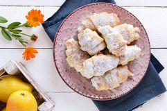 Homemade croissants with fruit jam, decorated with powdered sugar on a ceramic plate Stock Images