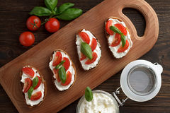 Homemade crusty bruschetta with feta, tomato and basil on wooden cutting board. Stock Image