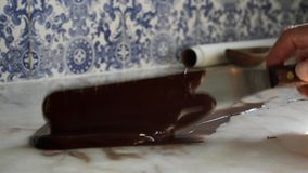 Homemade culinary artisan tempering smooth dark chocolate Confectionery on marble counter with blue and white tiles in background stock video