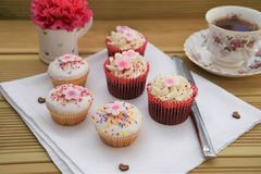 Homemade cup cakes with iced pink flower decorations and cup of tea. Homemade and baked cupcakes with icing and buttercream, some vanilla sponge and some Royalty Free Stock Photography