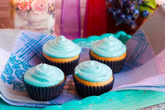 Homemade cupcakes with mint cream towel. Homemade muffins on a blue waffle towel Stock Photos