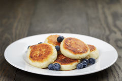 Homemade curd fritters on plate with berries Stock Photography