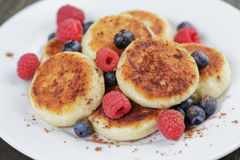 Homemade curd fritters on plate with berries Stock Images