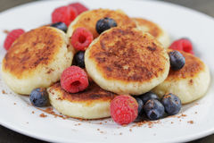 Homemade curd fritters on plate with berries Royalty Free Stock Images