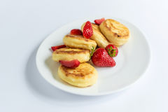 Homemade curd fritters with strawberry on a white plate Royalty Free Stock Photos