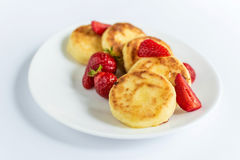 Homemade curd fritters with strawberry on a white plate Stock Images
