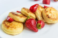 Homemade curd fritters with strawberry on a white plate Stock Photo