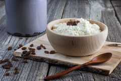 Homemade curd in a wooden bowl with raisins and wooden spoon royalty free stock photo