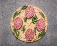 Homemade cutlet of beef for burgers, lined circle on a round wooden chopping board parsley and dill and spices. Homemade cutlet of beef for burgers, lined circle Stock Photo