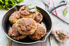 Homemade cutlets, roasted or baked in black cast-iron skillet. Wooden table, fresh vegetables and parsley Stock Photography
