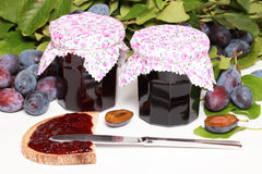 Homemade damson jam. Two glasses of homemade damson jam with fresh fruits and leaves stock image