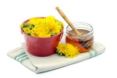 homemade Dandelion honey in a glass and flower heads of dandelion. isolated white background royalty free stock photography