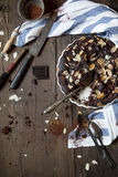Homemade dark chocolate and almonds cake on wooden table Royalty Free Stock Images