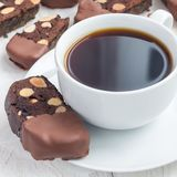 Homemade dark chocolate biscotti cookies with almonds, covered with melted chocolate, and cup of coffee, square format royalty free stock photography