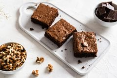 Homemade dark chocolate brownies on white table. Delicious bitter sweet and fudge. Chocolate cake royalty free stock image