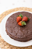 Homemade dark chocolate cake decorated with cocoa and fresh organic strawberries on top served on a white plate and. Straw tablemat Royalty Free Stock Photos
